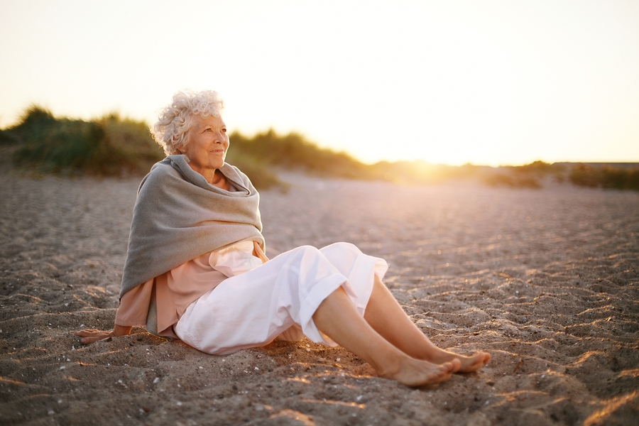 Relaxed Elderly Woman Sitting On The Beach